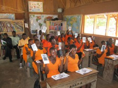 Students in Ghana holding up their e-readers