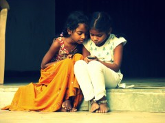 2 curious kids peering into a cell phone.