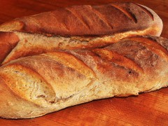 two loaves of fresh baked bread on wooden surface